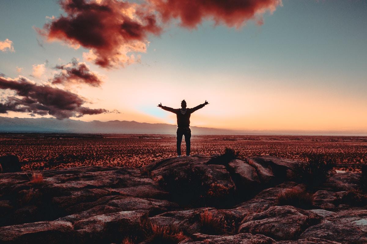 Un homme est très heureux au sommet d'une montagne, les bras